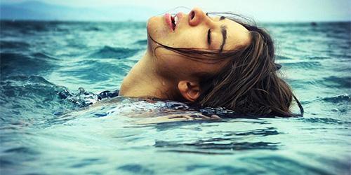 Девушка плавает в морской воде