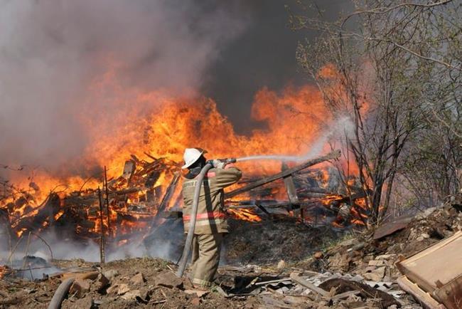 Пожарник тушит горящее здание