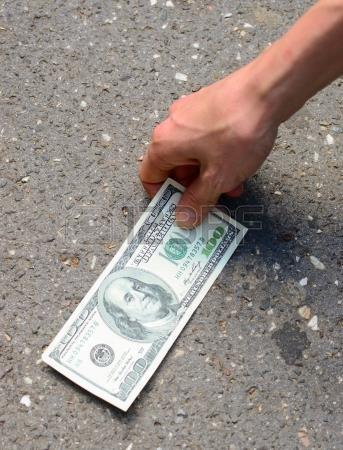 Стодолларовая купюра на асфальте