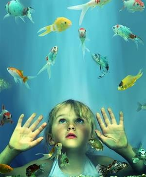 Девочка смотрит на рыбок
