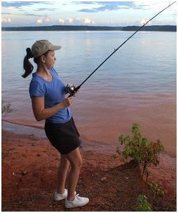 Женщина ловит рыбу на удочку