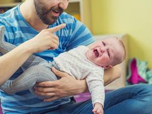 Ребенок плачет на руках у мужчины