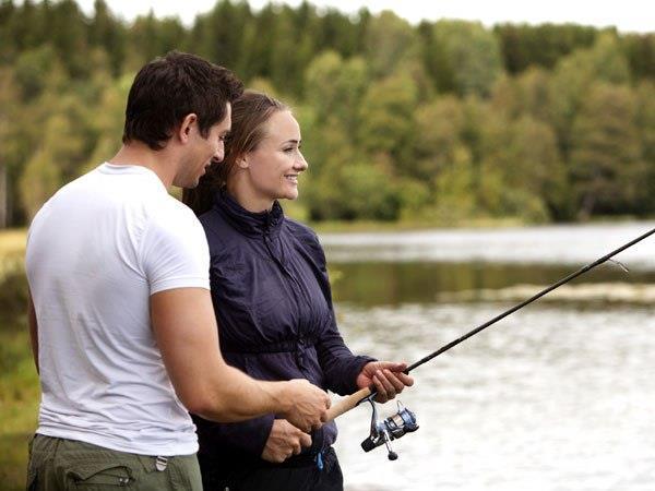 Мужчина учит женщину ловить рыбу