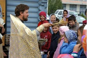 Священник кропит водой